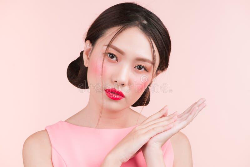 Ritratto di bellezza del fronte asiatico femminile sopra il fondo rosa di colore immagini stock
