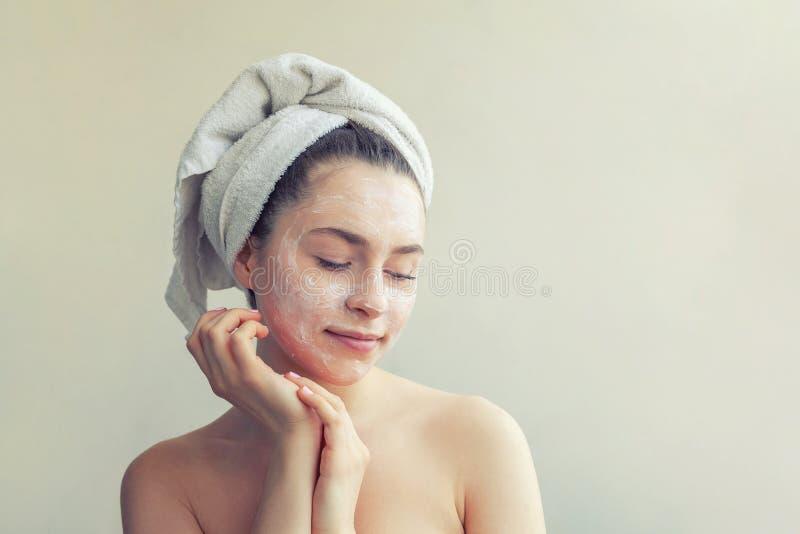 Ritratto di bellezza della donna in asciugamano sulla testa con la maschera di nutrizione bianca o sulla crema sul fronte, fondo  fotografia stock