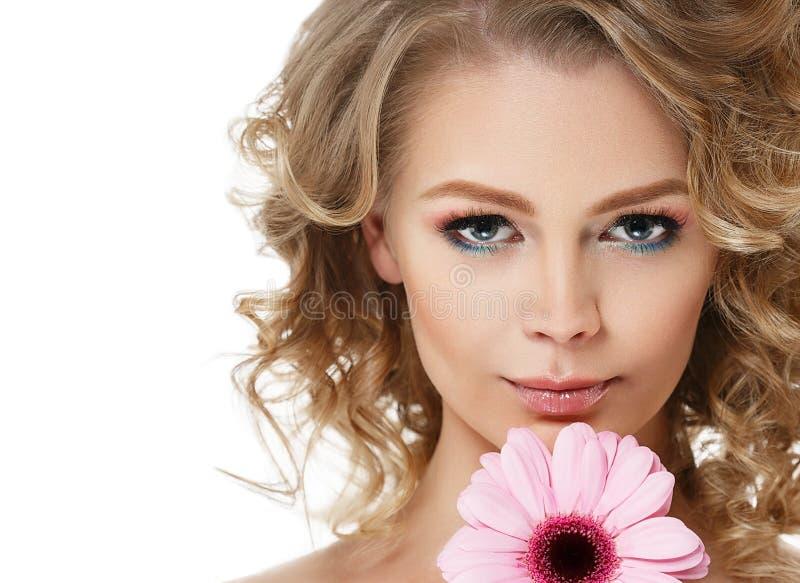 Ritratto di bellezza della donna con il fiore in capelli biondi ricci dei capelli isolati su bianco immagini stock