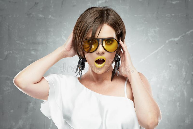 Ritratto di bellezza della giovane donna con i vetri di sole gialli Touchi della mano immagine stock libera da diritti
