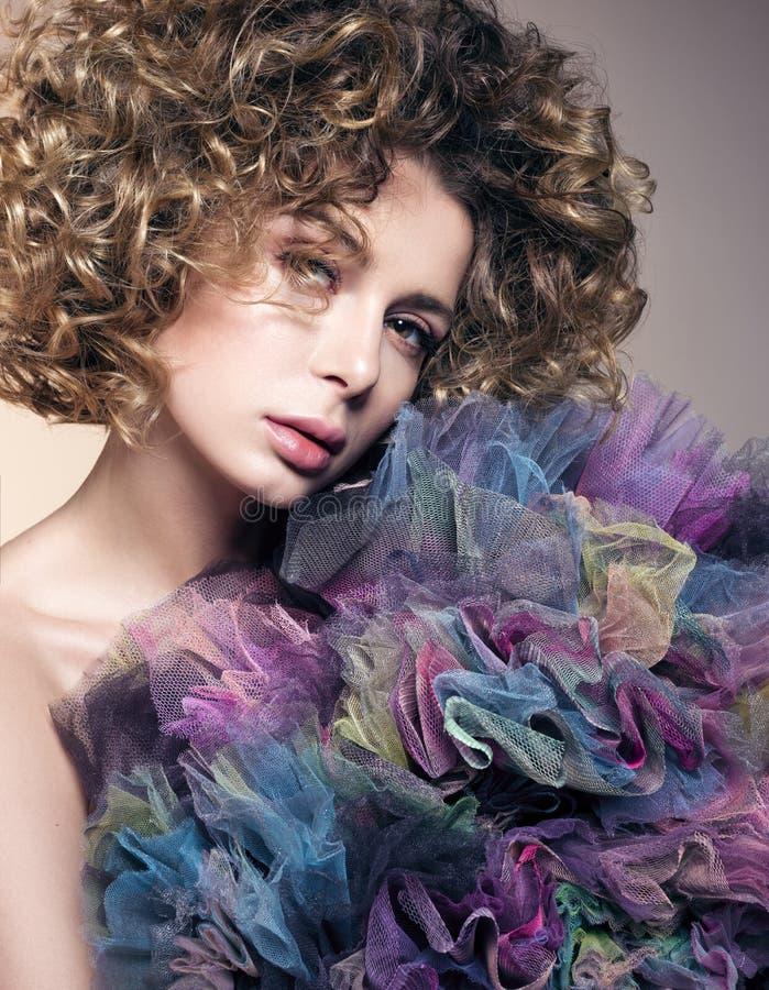 Ritratto di bellezza della giovane donna con il bello tessuto netto del poliestere e dei capelli ricci immagini stock