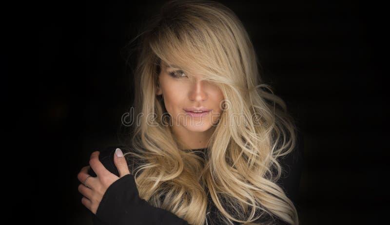 Ritratto di bellezza della giovane donna elegante Fondo scuro Ragazza che esamina macchina fotografica Trucco di fascino fotografia stock libera da diritti