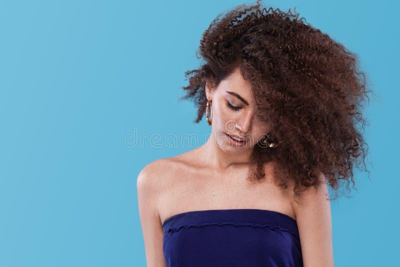 Ritratto di bellezza della ragazza con l'acconciatura di afro Ragazza che posa sul fondo blu Colpo dello studio Copi lo spazio fotografia stock