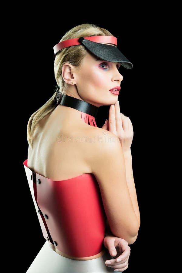 Ritratto di bellezza di bella giovane donna in colori dei vestiti di progettista rosso di plastica e grigio e visiera Fondo isola fotografia stock