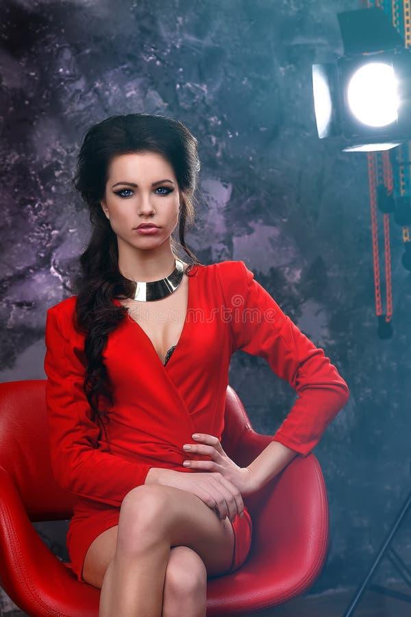 Ritratto di bellezza di bello castana sexy in un vestito rosso su un fondo grigio fotografia stock libera da diritti