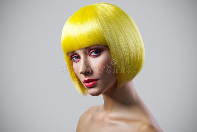 Ritratto di bellezza di giovane modello femminile sveglio calmo con le lentiggini, il trucco rosso e la parrucca gialla esaminant fotografia stock