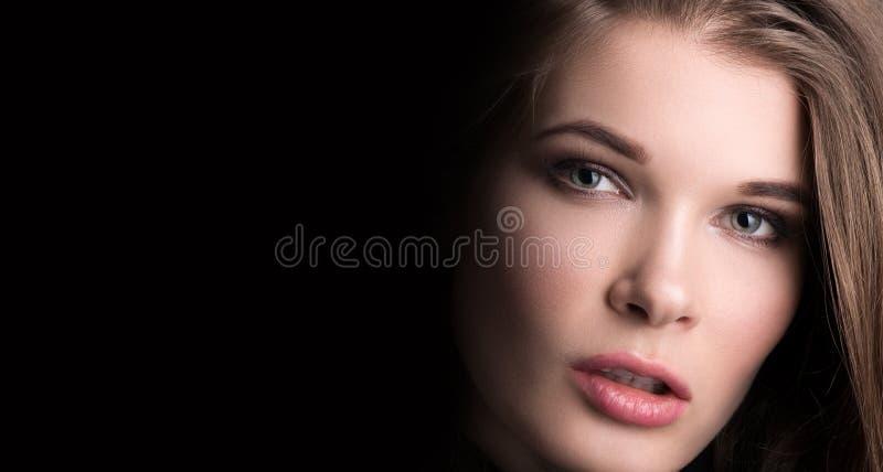 Ritratto di bellezza Il fronte di giovane bello primo piano della donna su fondo nero immagine stock