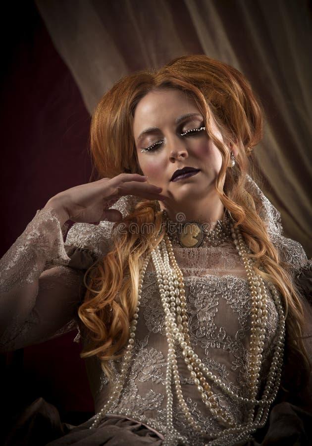 Ritratto di bellissima donna coi capelli rossi vestita in costume da tipografo come Elizabeth I immagini stock