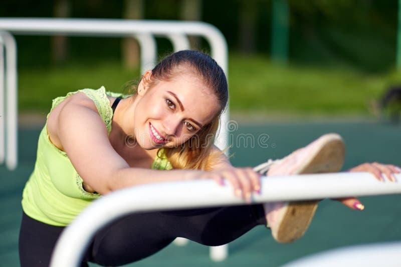Ritratto di bello addestramento d'allungamento sorridente della donna della ginnasta o del danser in campo sportivo di allenament immagine stock libera da diritti