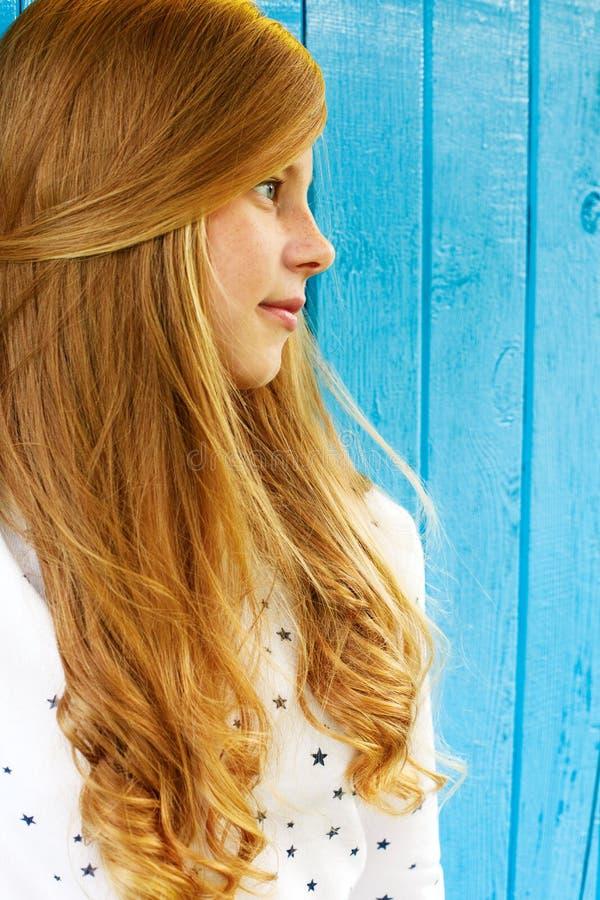 Ritratto di bello adolescente biondo su una parete blu immagini stock libere da diritti