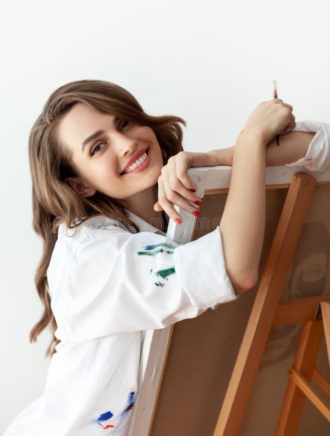 Ritratto di bello artista felice con il suo materiale illustrativo allo studio immagini stock