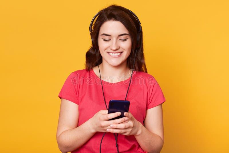 Ritratto di bello ascoltare moro la musica sul telefono cellulare, stante contro il fondo giallo che porta maglietta rossa, fotografia stock libera da diritti