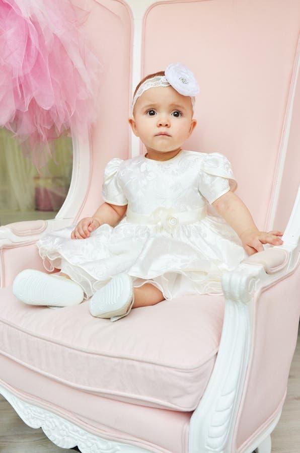 Ritratto di bello babygirl in vestito bianco sulla sedia rosa nello studio Bambini svegli immagine stock