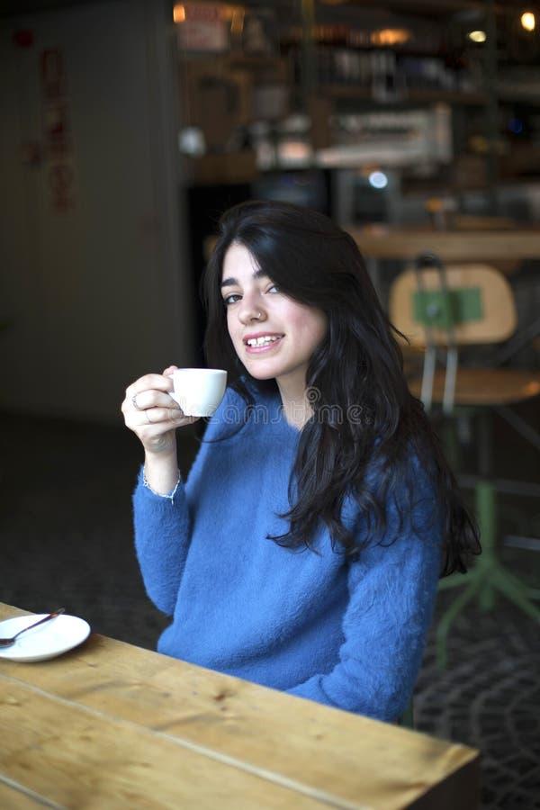 Ritratto di bello caffè bevente sorridente e di esame della giovane signora della macchina fotografica mentre sedendosi alla tavo fotografia stock libera da diritti