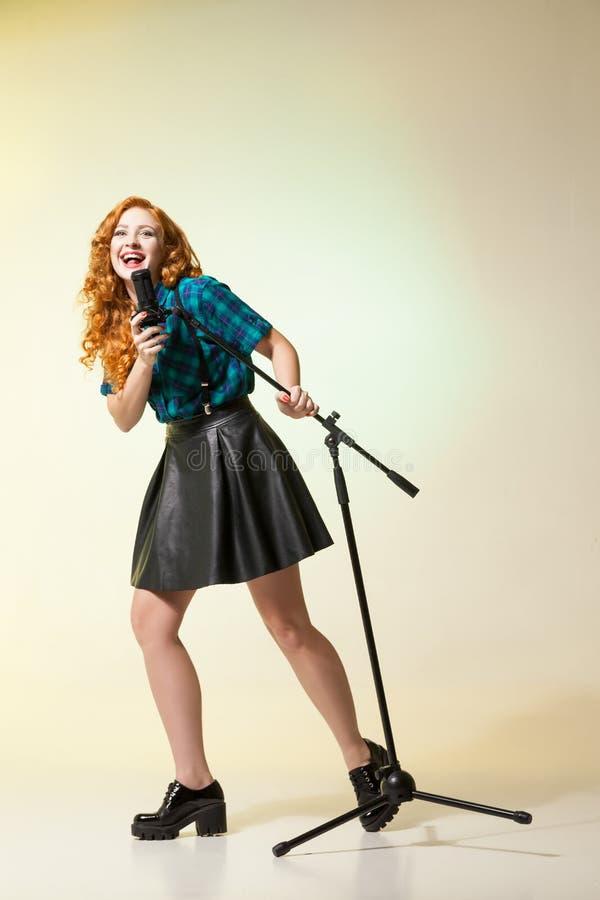 Ritratto di bello canto alla moda del cantante nel mic immagine stock