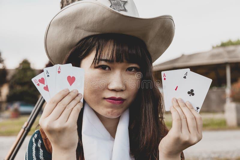 Ritratto di bello cowgirl femminile cinese che gioca con le carte del poker fotografia stock