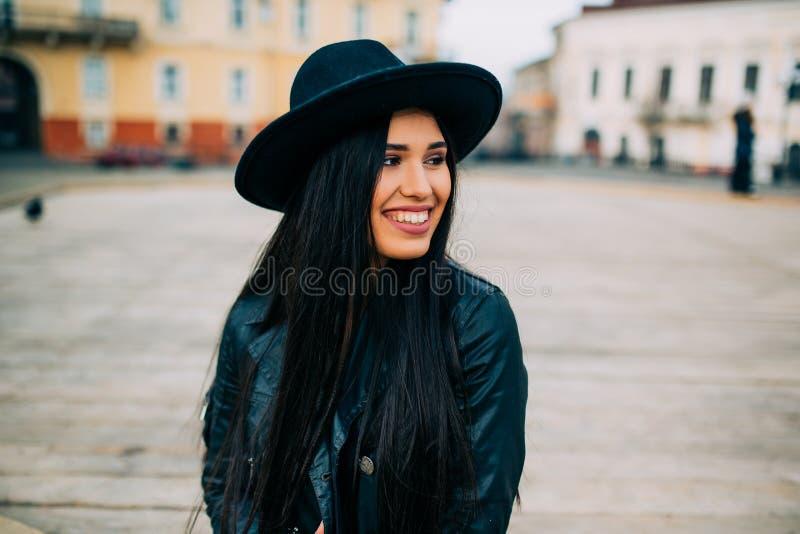 Ritratto di bello giovane castana con black hat posando in rivestimento un black hat sulla via della città della molla fotografia stock libera da diritti