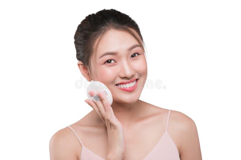 Ritratto di bello giovane modello asiatico che applica un certo usi della polvere fotografie stock libere da diritti