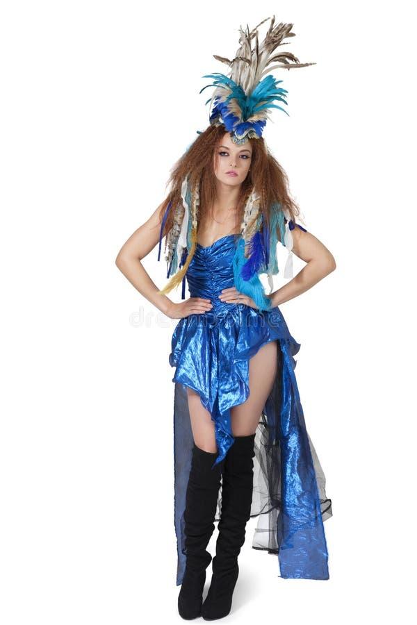Ritratto di bello giovane modello di moda che posa con il copricapo della piuma sopra fondo bianco fotografia stock libera da diritti
