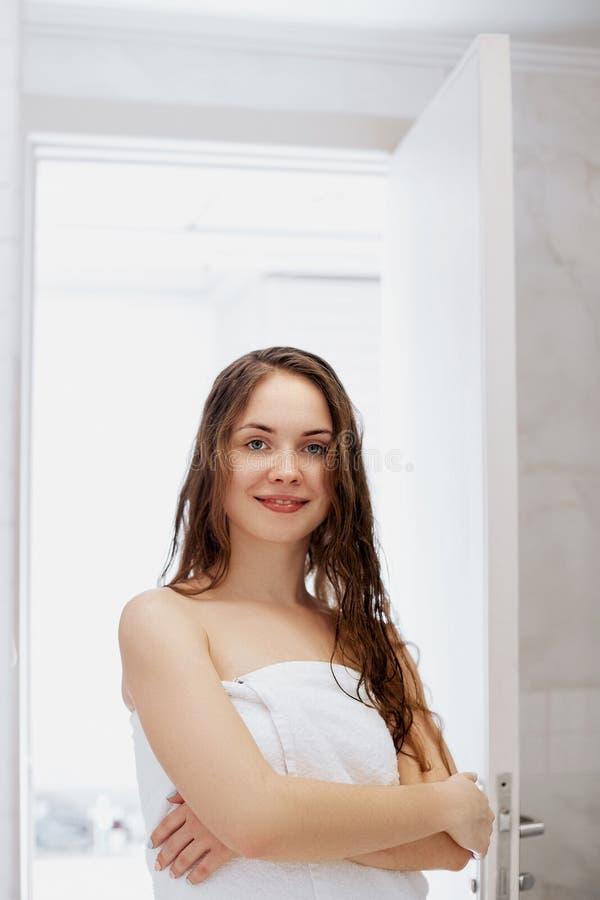 Ritratto di bello giovane modello femminile nel bagno che applica olio per capelli Primo piano della donna sexy in asciugamano ch fotografia stock