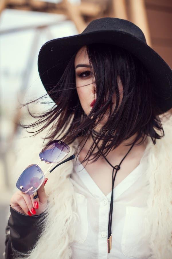 Ritratto di bello modello in pelliccia, cappello ed occhiali da sole Urb fotografia stock libera da diritti