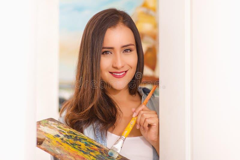Ritratto di bello pittore della giovane donna con il pennello della tavolozza e di colore a disposizione, in un fondo vago fotografie stock libere da diritti