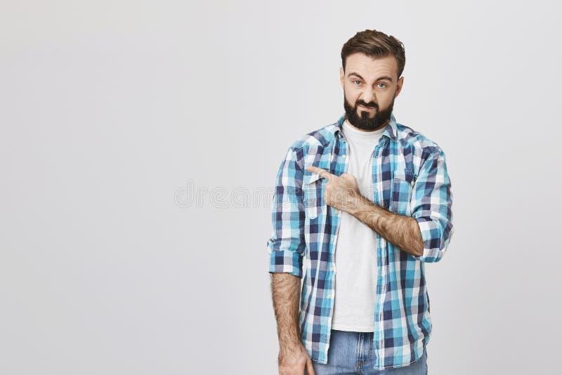 Ritratto di bello tipo barbuto caucasico, esprimendo repulsione e rabbia mentre indicando a sinistra con una mano, più fotografie stock libere da diritti
