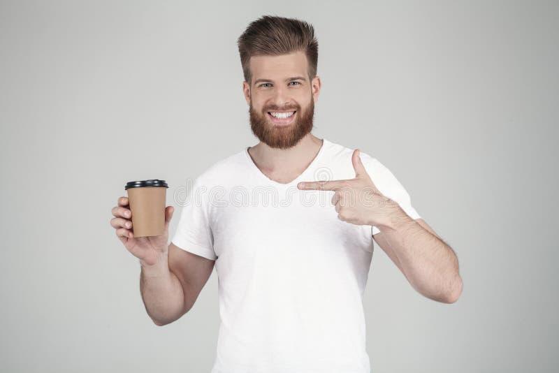 Ritratto di bello uomo barbuto sexy vestito in una maglietta bianca con i suoi punti della mano a sorridere della tazza di caffè  fotografia stock