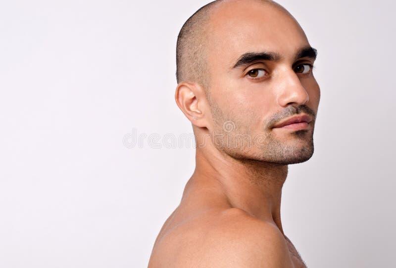 Ritratto di bello uomo calvo che esamina la sua spalla. immagini stock
