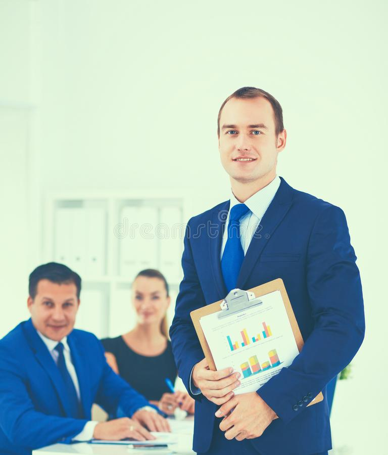 Ritratto di bello uomo d'affari che sta nell'ufficio con i colleghi immagine stock libera da diritti