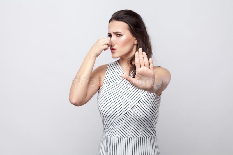 Ritratto di blocco di giovane donna castana della donna con trucco e la condizione a strisce del vestito con il gesto di arresto  immagine stock libera da diritti