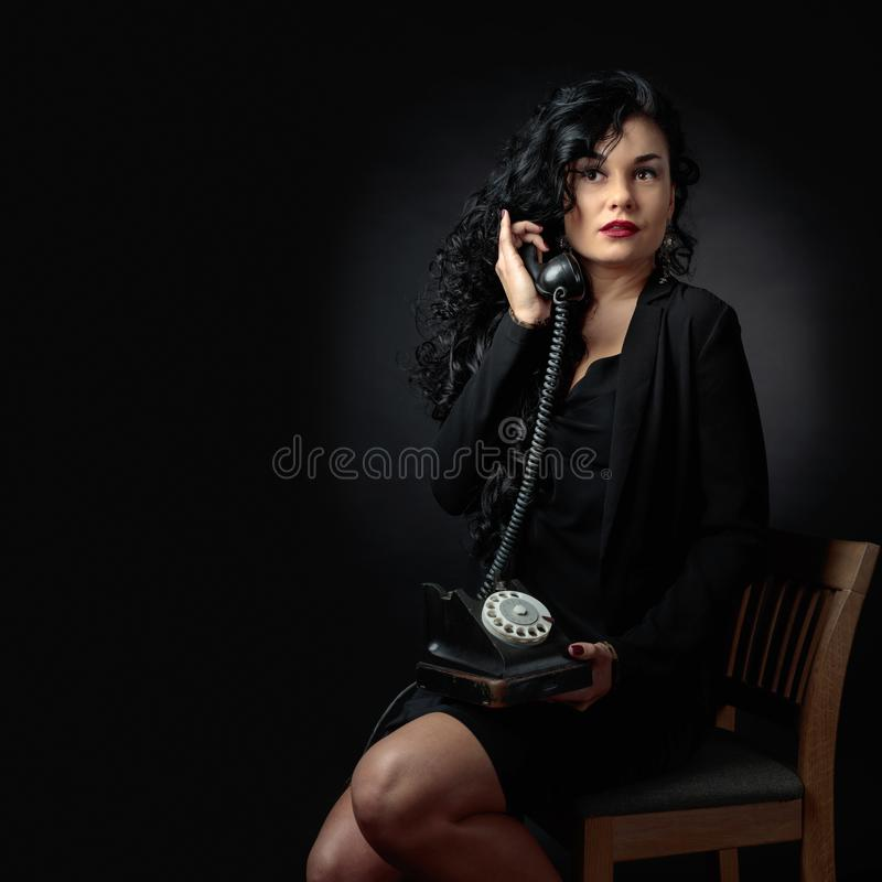 Ritratto di castana attraente con il vecchio telefono su un bacground nero immagini stock libere da diritti