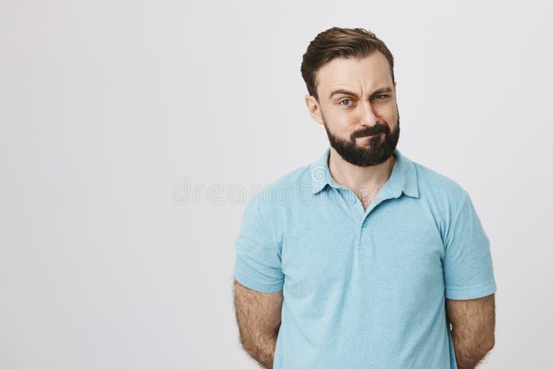 Ritratto di castana bello con la barba ed i baffi vicino alla parete bianca Il suo sopracciglio alzato mostrando il suo interesse immagini stock