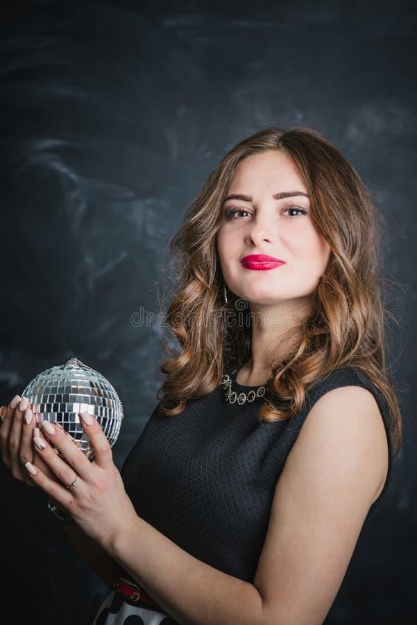 Ritratto di castana in vestito nero con la palla della discoteca a disposizione immagine stock libera da diritti