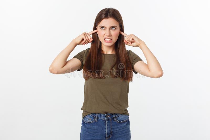 Ritratto di chiusura di una giovane donna arrabbiata che si copre le orecchie, smette di fare quel rumore forte e mi fa venire il immagine stock
