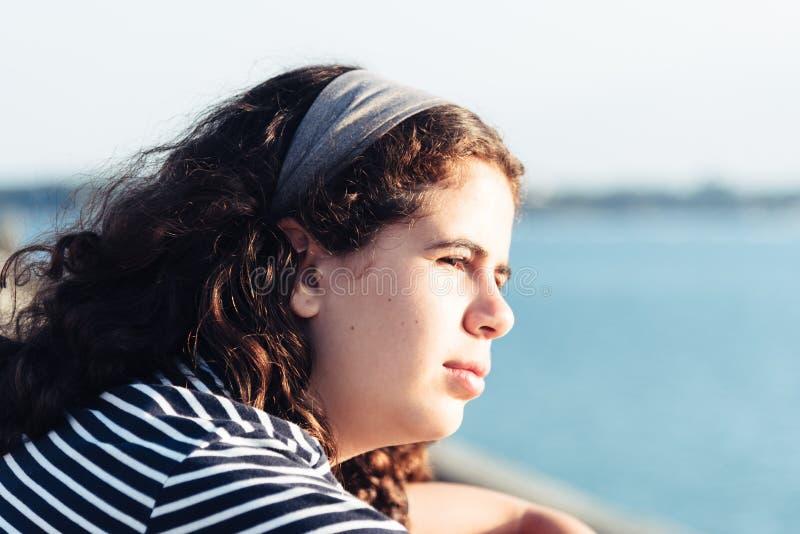 Ritratto di colpo in testa di bella ragazza che esamina il mare contro il sole fotografia stock