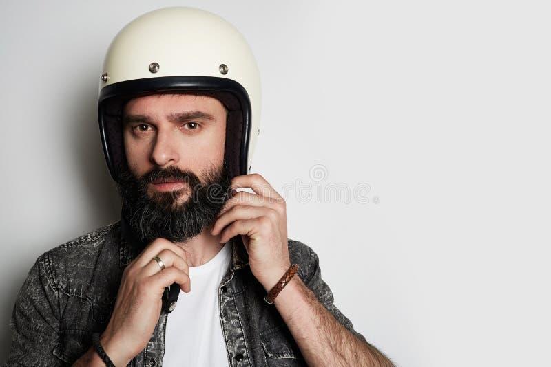 Ritratto di colpo in testa del modello maschio barbuto brutale in camicia nera dei jeans che esamina macchina fotografica sopra f immagini stock