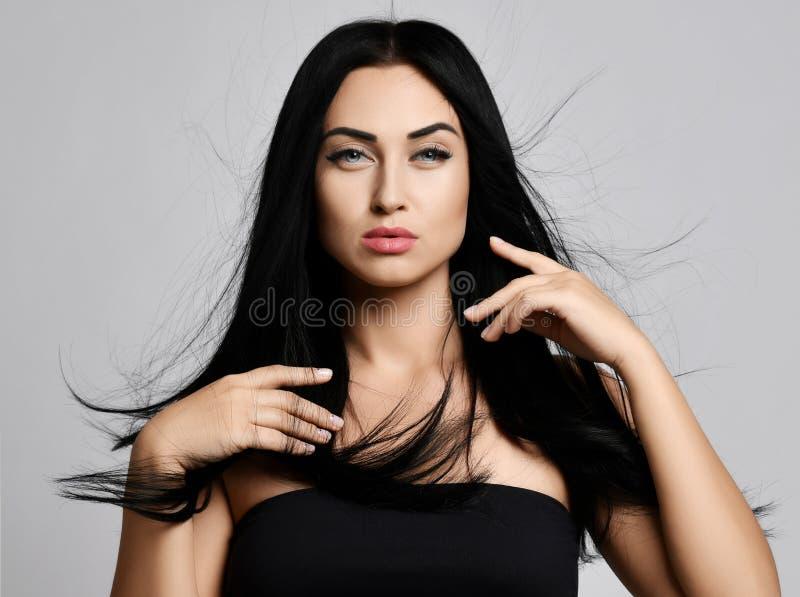 Ritratto di concetto della pubblicità della donna castana spazzolando delicato i suoi capelli perfetti che fluttuano nel vento co fotografia stock