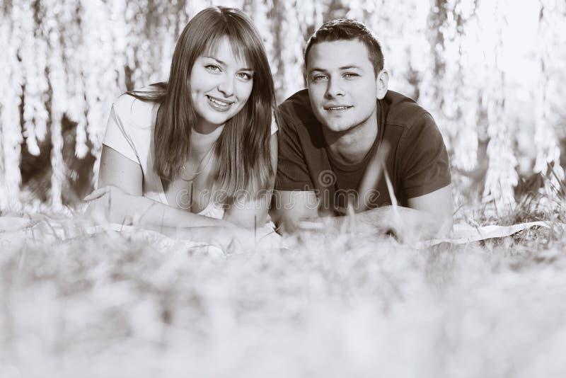 Ritratto di couplelaying allegro sull'erba fotografia stock