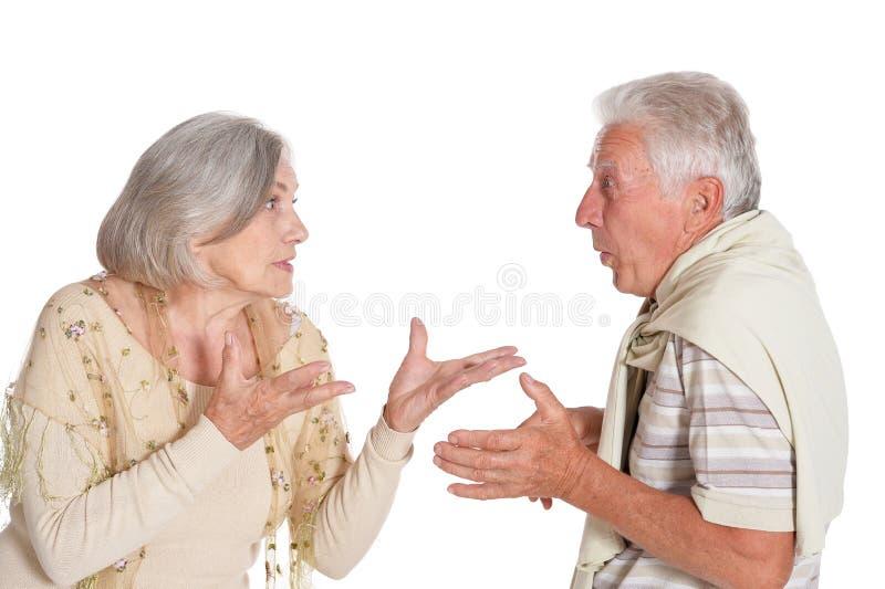 Ritratto di discussione delle coppie senior su fondo bianco immagine stock
