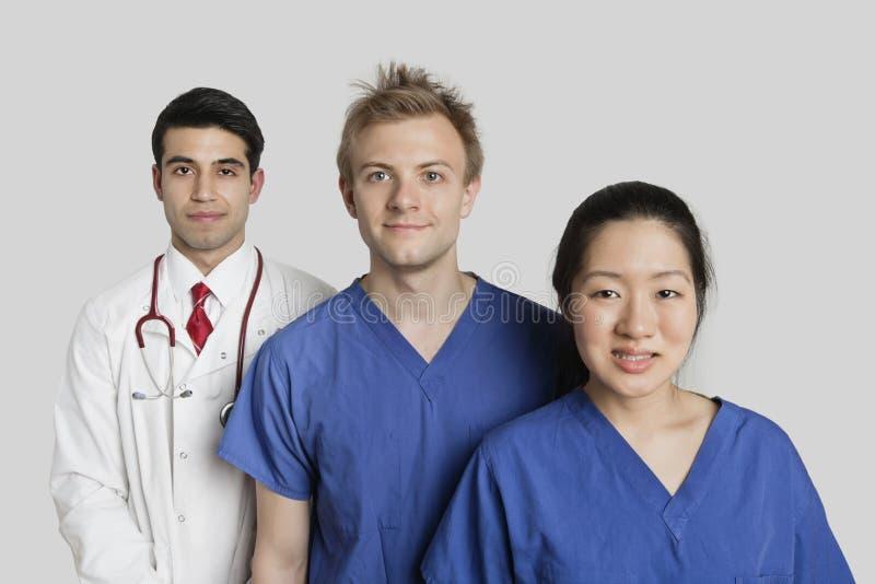 Ritratto di diverso gruppo di medici che controlla fondo grigio fotografia stock