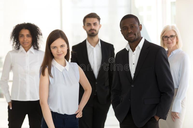 Ritratto di diverso gruppo sicuro del lavoro che esamina macchina fotografica immagini stock