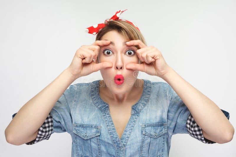 Ritratto di domandarsi bella giovane donna in camicia blu casuale del denim con trucco, condizione rossa della fascia, facente gl fotografia stock libera da diritti