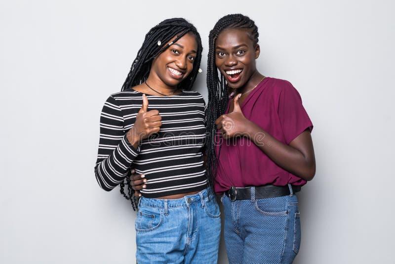 Ritratto di due amiche africane che mostrano i pollici sul segno su fondo grigio fotografie stock