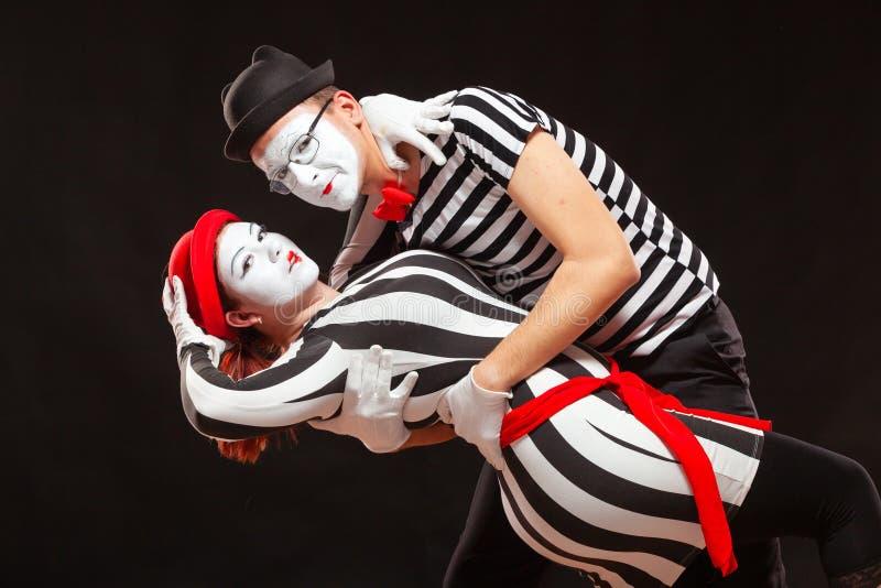Ritratto di due artisti che si esibiscono, isolati su fondo nero L'uomo che sta appoggiando la donna mentre danza Simbolo di immagini stock