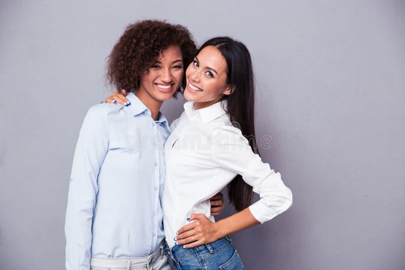 Ritratto di due ragazze sorridenti che stanno insieme immagini stock
