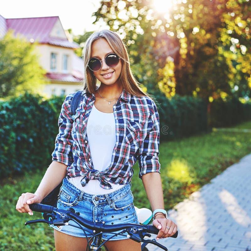 Ritratto di estate della ragazza graziosa su una bicicletta immagine stock libera da diritti