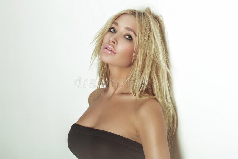 Ritratto di fascino della donna bionda sexy. Capelli ricci lunghi. C abbronzata fotografia stock