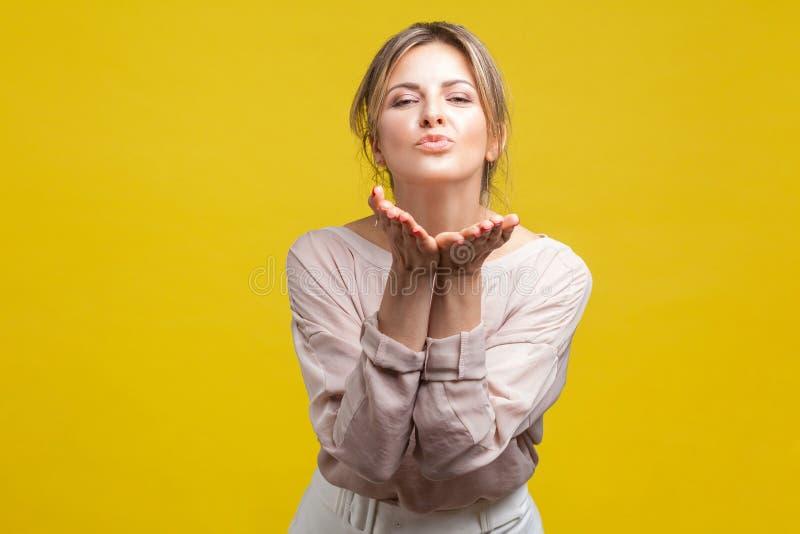 Ritratto di felice in amore di bella donna con capelli biondi con camicetta di beige, isolata su fondo giallo fotografia stock