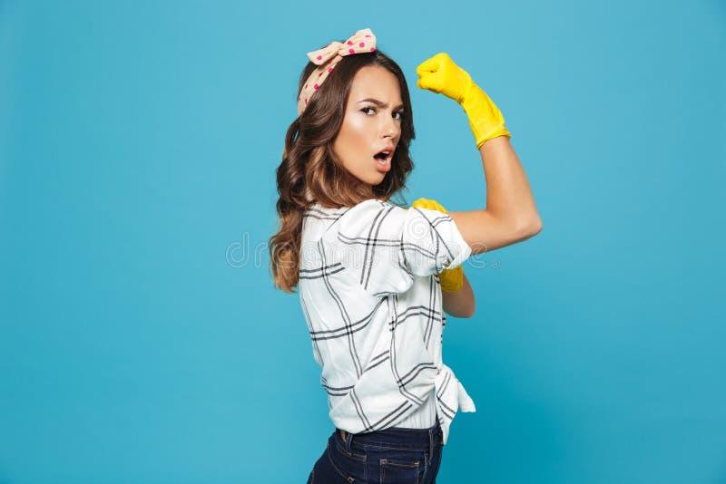 Ritratto di forte giovane donna 20s che mostra bicipite mentre indossando y fotografia stock